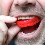 Close up of man using red mouthguard