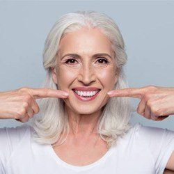 Older woman pointing to beautiful smile after implant denture placement