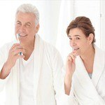 Older man and woman brushing teeth together after implant denture placement