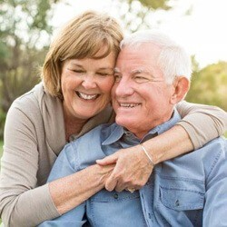 An older couple smiling and hugging outside
