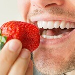 A man eating a strawberry