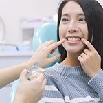 dentist helping patient with dental implant