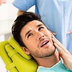 Man on dental chair holding cheek in pain