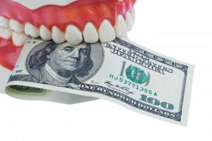 A set of false teeth holding a one-hundred dollar bill.
